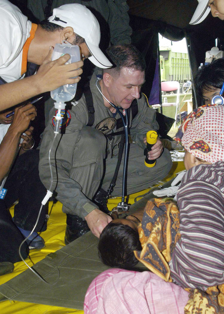 US Navy (USN) Lieutenant (LT) Mark Banks, tends to a patient flown-in by a USN helicopter to a temporary triage site set up in Aceh, Sumatra, Indonesia. Medical teams from USS ABRAHAM LINCOLN (CVN 72) [not shown], Carrier Air Wing 2 (CVW-2) and the International Organization for Migration (IOM) set-up a triage site on Sultan Iskandar Muda Air Force Base (AFB), in Banda Aceh, Sumatra