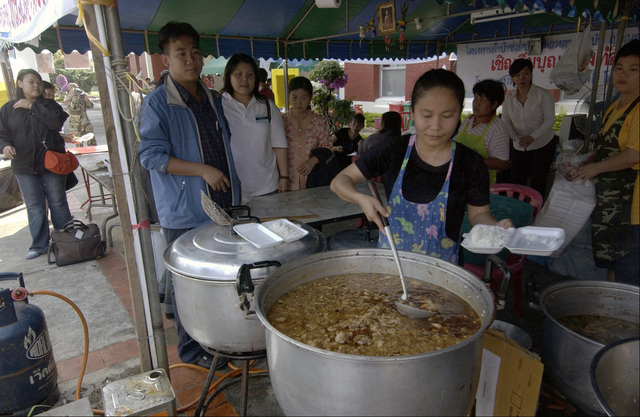 A local volunteer prepares hot meals at a food station at Phuket International Airport, Thailand, on Jan. 4, 2005. The food station feeds hundreds of meals to both tsunami victims and relief volunteers daily free of charge. (USAF PHOTO by TECH. SGT John M. Foster) (Released)