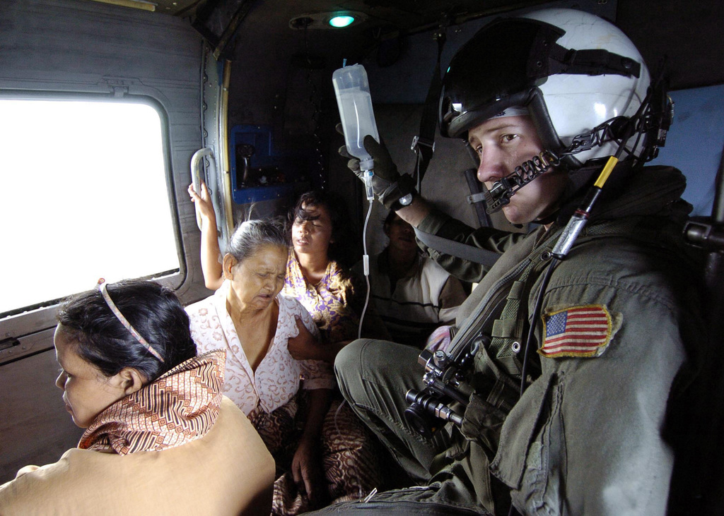US Navy (USN) Air Crewman Matt Gardner, assigned to the Saberhawks of Anti-Submarine Squadron Light Four Seven (HSL-47), holds the IV bottle of an ill Indonesian woman during a humanitarian aid mission to Aceh, Sumatra, Indonesia (IDN). Helicopters and aircraft assigned to the aircraft carrier USS ABRAHAM LINCOLN (CVN-72) are conducting humanitarian operations in the wake of the Tsunami that struck South East Asia