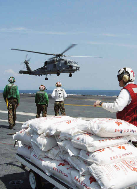 Bags of rice wait to be loaded onto a US Navy (USN) SH-60B Sea Hawk helicopter, assigned to the Saberhawks of Helicopter Anti-Submarine Squadron Light Four Seven (HSL-47), as it lands on board the nuclear-powered aircraft carrier USS ABRAHAM LINCOLN (CVN-72). Helicopters assigned to Carrier Air Wing Two (CVW-2) are supporting Operation UNIFIED ASSISTANCE