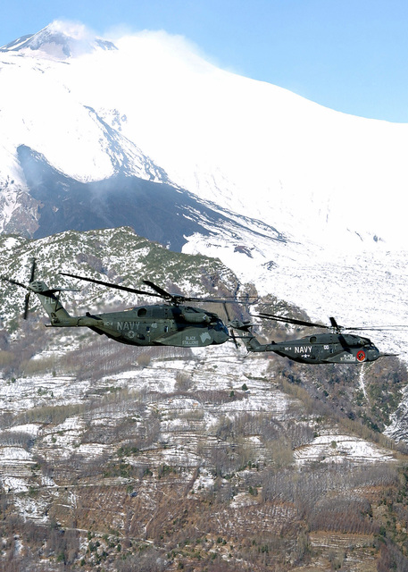 Two US Navy (USN) MH-53E Sea Dragon helicopters, Helicopter Combat Support Squadron 4 (HC-4), Black Stallions, Naval Air Station Sigonella, Sicily (SIC), fly in formation in front of Mount Etna, the largest active volcano in Europe