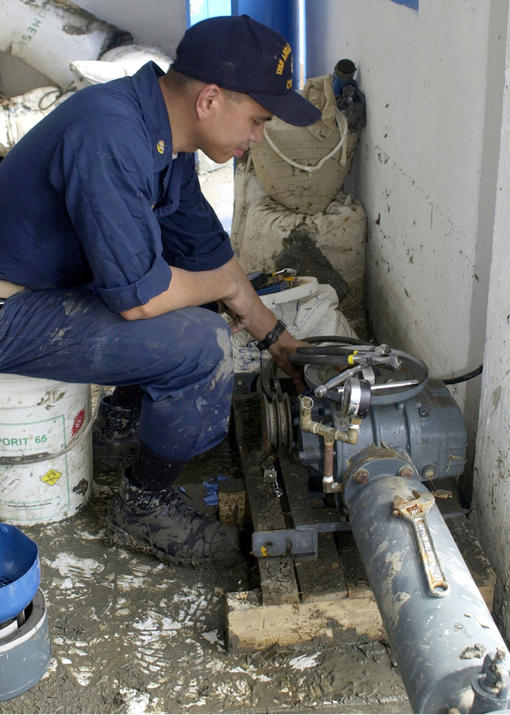 US Navy (USN) CHIEF Electrician's Mate (EM) Conrad Capindo, works to repair a generator that will pump fresh drinking water into a devastated hospital in Banda Aceh, Sumatra, Indonesia (IDN), during Operation UNIFIED ASSISTANCE