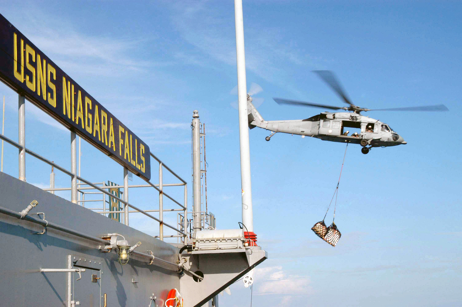 A US Navy (USN) MH-60S Knighthawk helicopter assigned to the Providers of Helicopter Combat Support Squadron (HC-5), Detachment 3, transfers stores from the Military Sealift Command (MSC) Combat Stores Ship (TAFS) USNS NIAGRA FALLS (T-AFS 3) during an at sea Vertical Replenishment (VERTREP).  This ship is currently operating in the Indian Ocean off the waters of Indonesia and Thailand in support of Operation Unified Assistance, for Tsunami victims