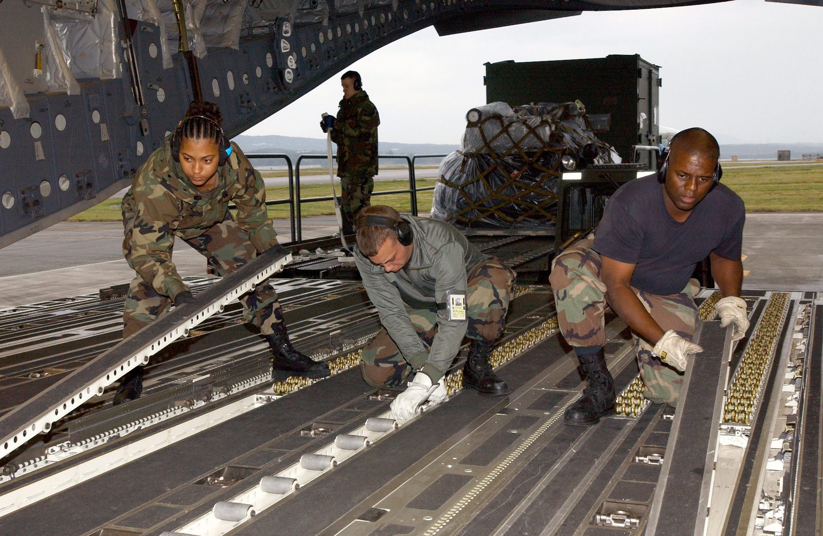 (From left-to-right), U.S. Air Force SENIOR AIRMAN Aqueelah Lucas, AIRMAN 1ST Class James Miller and STAFF SGT. Robert Carter, all members of the 733rd Air Mobility Squadron, Kadena Air Base (AB), Japan, reconfigure the floor C-17 Globemaster III cargo aircraft from the 62nd Airlift Wing, McChord Air Force Base, Wash., during Operation Unified Assistance at Kadena AB on Jan. 9, 2005. More than 18,000 U.S. military personnel are providing humanitarian assistance in Southwest Asia after a 9.0 magnitude earthquake on Dec. 26, 2004, triggered devastating tsunamis that killed over 250,000 people in the region. (USAF PHOTO by AIRMAN 1ST Class Michael Pallazola) (Released)