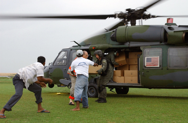 U.S. Air Force TECH. SGT.  Keith Kolb (right), from the 33rd Rescue Squadron (RQS), Kadena Air Base, Japan, and Sri Lankan Air Force Flight Lieutenant Chamila Manatunga (inside the helicopter), help Sri Lankan workers and Red Cross volunteers unload hygiene kits from an HH-60 Pavehawk helicopter from the 33rd RQS during Operation Unified Assistance at Pottuville, Sri Lanka, on Jan. 9, 2005. More than 18,000 U.S. military personnel are providing humanitarian assistance in Southwest Asia after a 9.0 magnitude earthquake on Dec. 26, 2004, triggered devastating tsunamis that killed over 250,000 people in the region. (USAF PHOTO by STAFF SGT. Chenzira Mallory) (Released)
