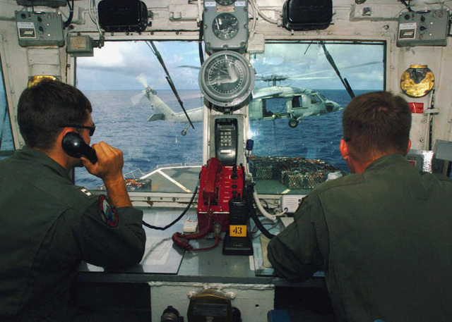 US Navy (USN) Lieutenant (LT) Todd Pike and Lieutenant JG (LTJG) Thomas Neill, assigned to Helicopter Combat Support Squadron 5 (HC-5), man the flight control tower as an MH-60S Sea Hawk helicopter lifts cargo from the Military Sealift Command (MSC) Combat Stores Ship USNS CONCORD (T-AFS 5), in support of Operation UNIFIED ASSISTANCE
