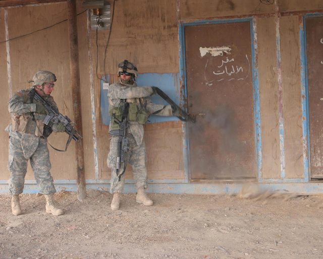 A U.S. Army Soldier with Bravo Company, 2nd Battalion 1ST Infantry Regiment,  blows off the lock of a door during a raid in Anah, Iraq.  2/1 is deployed in support of Operation Iraqi Freedom to conduct counter-insurgency operations to isolate and neutralize anti-Iraqi forces; support Iraqi reconstruction and democratic elections; and to facilitate the creation of a secure environment that enables Iraqi self-reliance and self-governance. (U.S. Marine Corps photo by Lance CPL. Sheila M. Brooks) (Released)