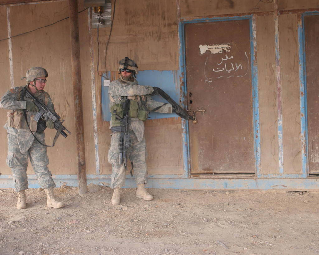 A U.S. Army Soldier with Bravo Company, 2nd Battalion 1ST Infantry Regiment,  prepares to blow off the lock of a door during a raid in Anah, Iraq.  2/1 is deployed in support of Operation Iraqi Freedom to conduct counter-insurgency operations to isolate and neutralize anti-Iraqi forces; support Iraqi reconstruction and democratic elections; and to facilitate the creation of a secure environment that enables Iraqi self-reliance and self-governance. (U.S. Marine Corps photo by Lance CPL. Sheila M. Brooks) (Released)