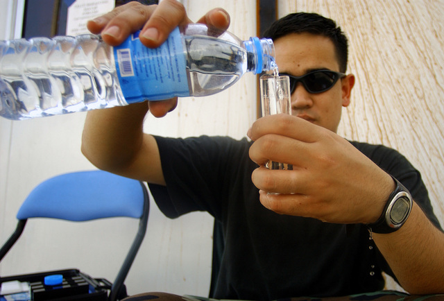 U.S. Air Force STAFF SGT. Dudley Lykins, from the 60th Aerospace Medicine Squadron, Travis Air Force Base, Calif., test a water botttle for ph balance, chlorine, and bacteria during Operation Unified Assistance at Utapao Air Base, Thailand, on Jan. 13, 2005. More than 18,000 U.S. military personnel are providing humanitarian assistance in Southwest Asia after a 9.0 magnitude earthquake on Dec. 26, 2004, triggered devastating tsunamis that killed over 250,000 people in the region. (USAF PHOTO by STAFF SGT. Sarayuth Pinthong) (Released)