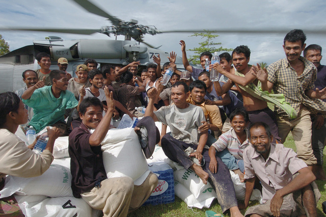Victims of the Tsunami rush a US Navy (USN) MH-60S Sea Hawk helicopter assigned to the Gunbearers of Helicopter Combat Support Squadron 11 (HC-11) as the crew offloads relief supplies