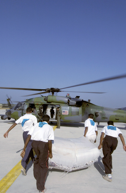 Relief workers prepare to load supplies onto an HH-60 Pave Hawk helicopter during Operation Unified Assistance at the Bandaranayake International Airport, Katunayake, Sri Lanka, on Jan. 15, 2005. (U.S. Air Force PHOTO by STAFF SGT. James Harper) (Released)