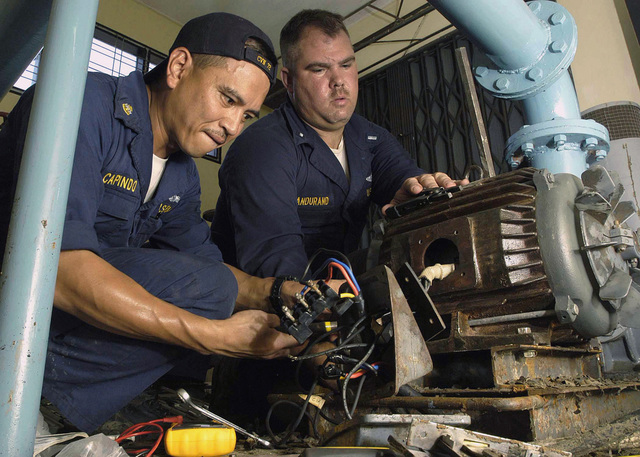 US Navy (USN) CHIEF Electrician's Mate (EMC) Conrad Capindo (left) and Lieutenant Junior Grade (LTJG) Brad Dandurand both deployed aboard the USS ABRAHAM LINCOLN (CVN 72) aircraft carrier, restore power to a hospital and the building's sewage plant, in support of Operation UNIFIED ASSISTANCE