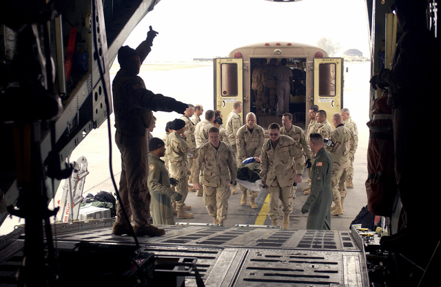 U.S. Air Force 332nd Contingency Aeromedical Staging Facility volunteers load patients onto an aircraft at Balad Air Base, Iraq, on 20 Jan 2005. (U.S. Air Force PHOTO by STAFF SGT. Neal X. Joiner) (Released)