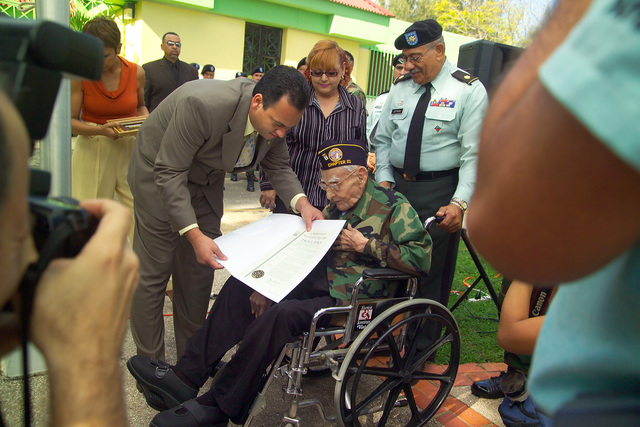 The Mayor of Vega Baja, Puerto Rico, Honorable Edgar Santana, presents Mr. Emiliano Mercado a proclamation for being the oldest living veteran, during the ceremony sponsored by the U.S. Army Volunteer Corps. (U.S. Army photo by Leo Martinez) (Released)