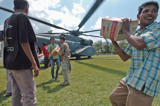 Indonesians civilians form a human chain to pass boxes of noodles from a US Navy (USN) MH-53E Sea Dragon helicopter, Helicopter Mine Countermeasures Squadron 15 (HM-15), Blackhawks, Naval Station (NS) Norfolk, Virginia (VA), bringing in relief supplies. The HM-15 is currently embarked on board the Wasp Class Amphibious Assault Ship USS ESSEX (LHD 2) [not shown], underway in support of Operation UNIFIED ASSISTANCE, the humanitarian operation effort in the wake of the Tsunami that struck South East Asia on December 26, 2004