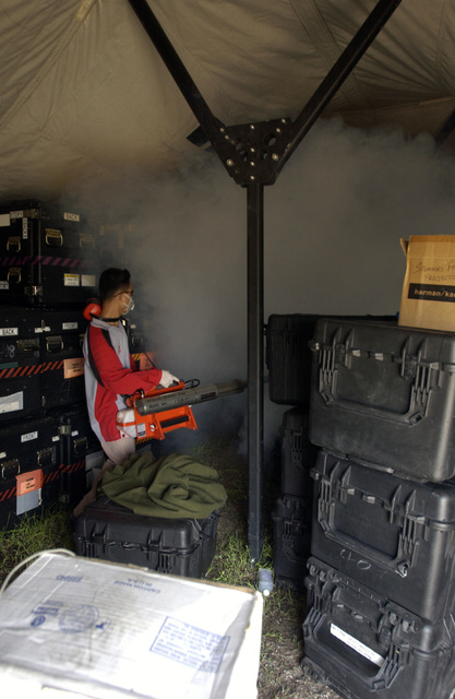 A Thai National dispenses a mosquito killing fog using a pulsFOG K-10 thermal fogging machine inside a tent during Operation Unified Assistance at Utapao Naval Air Station, Thailand,  on Jan. 24, 2005. (U. S. Air Force PHOTO by STAFF SGT. Shane Heiser) (Released)