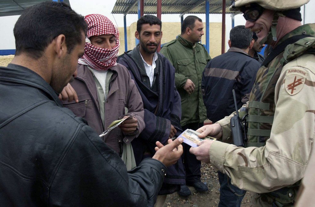 U.S. Army 350th Psychological Operations Company SGT. Eugene Thomas hands out flyers and stickers to Iraqi people at a water pumping station in Iraq, on Jan. 24, 2005, during Operation Iraqi Freedom. (U. S. Air Force PHOTO by AIRMAN 1ST Class Kurt Gibbons III) (Released)