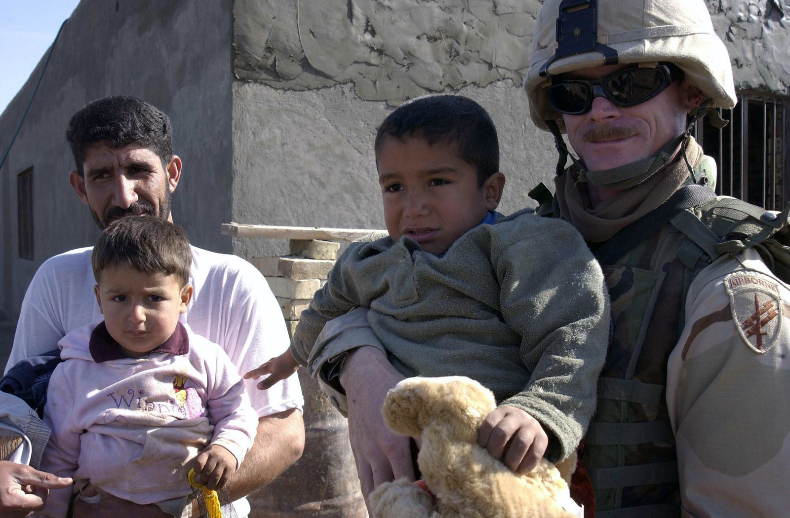 U.S. Army 350th Psychological Operations Company SGT. Eugene Thomas poses for a photograph with an Iraqi family near Logistics Support Area Anaconda, Iraq, on 26 Jan. 2005, during Operation Iraqi Freedom.  (U.S. Air Force PHOTO by AIRMAN 1ST Class Kurt Gibbons III) (Released)v