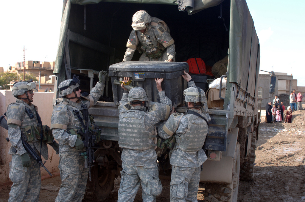 U.S. Army Soldiers of B Company, 2-22, 10th Mountain Division load back up supplies after a Medical and Civil Affairs Program (MEDCAP) which was conducted at an elementary school near Baghdad, Iraq on the of Jan. 27, 2006. MEDCAPs are continuously being carried out throughout Iraq as part of the humanitarian effort during Operation Iraq Freedom. (U.S. Army photo by SGT. 1ST Class David D. Isakson) (Released)