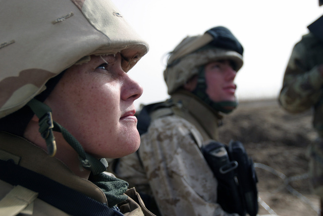 A female US Marine Corps (USMC) Marine assigned to Kilo Company, 3rd Battalion, 8th Marines, observes as security measures are installed at a schoolhouse, to be used as a polling site in the upcoming Iraqi elections, in Nasarwasalam, Iraq. The 1ST Marine Division is engaged in Security and Stabilization Operations (SASO), in the Al Anbar Province, Iraq, in support of Operation IRAQI FREEDOM