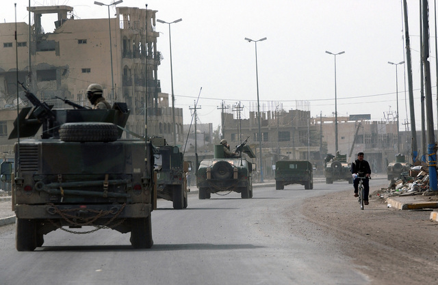 US Navy (USN) SEABEEs assigned to Naval Mobile Construction Battalion 7 (NMCB 7), Gulfport, Mississippi (MS), patrol the streets of Fallujah in armored High-Mobility Multipurpose Wheeled Vehicles (HMMWV). This is one day prior to Iraq's historic democratic elections. SEABEEs are providing additional security for Coalition camps and voting precincts