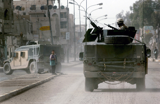 US Navy (USN) SEABEEs assigned to Naval Mobile Construction Battalion Seven (NMCB 7), Gulfport, Mississippi (MS), patrol the streets of Fallujah in armored High-Mobility Multipurpose Wheeled Vehicles (HMMWV). This is one day prior to Iraq's historic democratic elections. SEABEEs are providing additional security for coalition camps and voting precincts