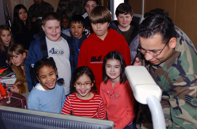 U.S. Air Force STAFF SGT. Patrick Zavala, a graphic designer from the 835th Communications Squadron, shows local elementary school children his designs on a computer during Job Shadow day at Ramstein Air Base, Germany, on Feb. 2, 2005. (U.S. Air Force PHOTO by AIRMAN Laura Simi) (RELEASED)