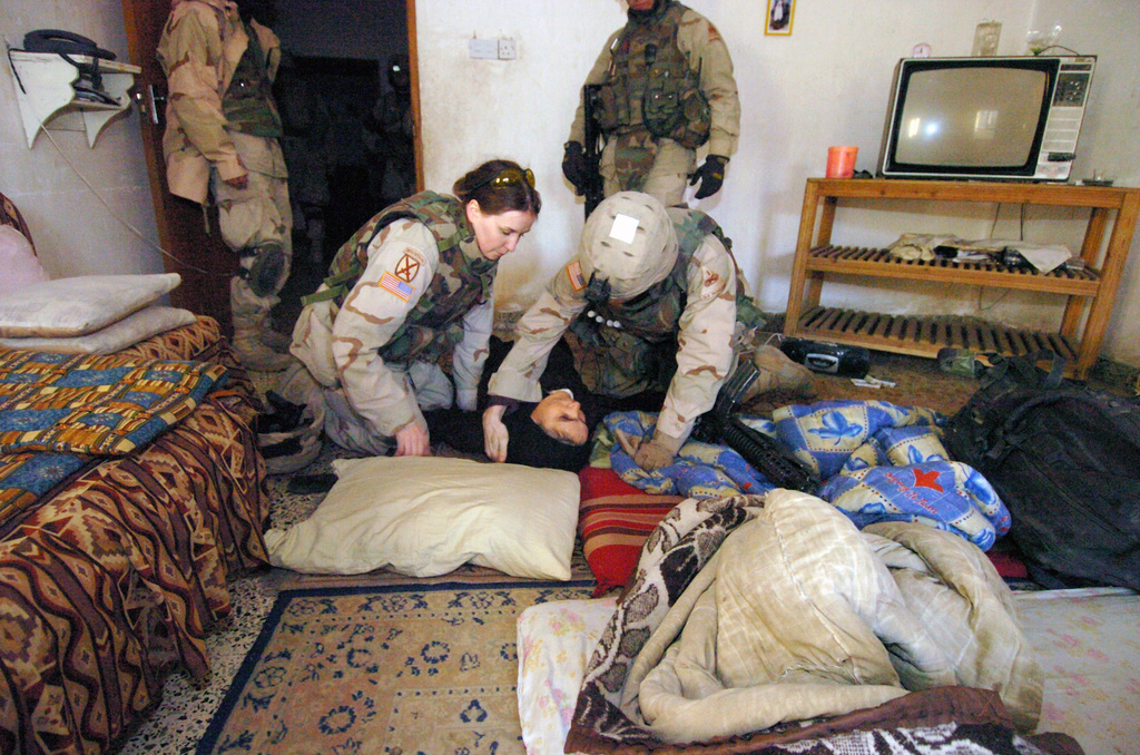US Army (USA) Soldiers assigned to 2nd Brigade Combat Team (BCT), 10th Mountain Division render aid to an Iraqi woman who fainted as member of the team conducted a search of her home located in Baghdad, Iraq. The 2nd BCT based out of Camp Victory, is conducting searches in local Baghdad communities for weapons that have been used against coalition forces, during Operation IRAQI FREEDOM