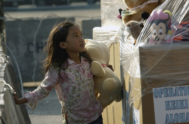 A Thai girl from Phuket, picks out a toy on the Chuc Sumet Porton pier in Sattahip, Thailand. The toys were donated by Military personnel stationed in Hawaii and were transferred to Thailand by the High Speed Vessel Two (HSV-2) SWIFT [not shown] as part of Operation UNIFIED ASSISTANCE