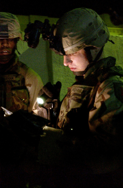 U.S. Army Soldiers from 1ST Squadron, 4th Calvary Regiment, 1ST Infantry Divison, read a map while patroling the streets of Poliwoda, Balad, Iraq, at night on Feb. 8, 2005. When elections where held in this city no one voted because the civic leader building was bombed and there where protests against the Iraqi government. (U.S. Air Force PHOTO by AIRMAN 1ST Class Kurt Gibbons III) (Released)