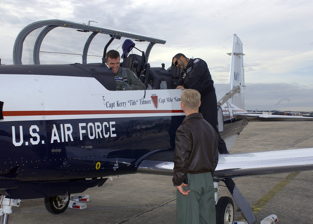 U.S. Air Force CAPT. Kerry Tidmore (seated inside the cockpit) is greeted by an AIRMAN after completing his T-6 Texan II aircraft certification at Randolph Air Force Base, Texas, on Feb. 10, 2005. He is training to be a member of the T-6 Demonstration Team that perform at air shows and other events throughout the country. (DOD PHOTO by David Terry) (Released)