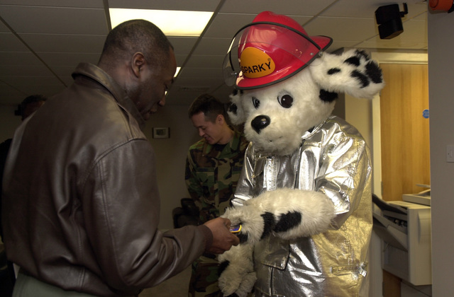 U.S. Air Force COL. Allen Kirkman, Jr., 460th Space Wing Commander, Buckley Air Force Base, Colo., receives a patch and coin from Sparky, the 48th Civil Engineer fire department mascot, during his visit at Royal Air Force (RAF) Lakenheath, England, on Feb. 10, 2005. RAF Lakenheath is currently involved in an Installation Excellence Awards inspection from Feb. 9-12, 2005. (U.S. Air Force PHOTO by AIRMAN 1ST Class William Shilling) (Released)