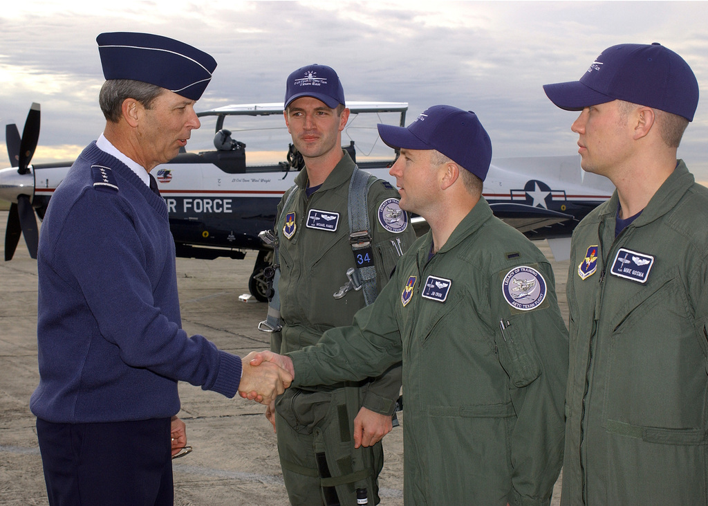 U.S. Air Force GEN. Donald Cook (left), Commander of the Air Education and Training Command, congratulates (from left-to-right) CAPT. Michael Rambo, 1ST LT. Jim Crum and 1ST LT. Mike Gosma, all members of the T-6 Texan II Demonstration Team, following a certification flight at Randolph Air Force Base, Texas, on Feb. 10, 2005. (DOD PHOTO by David Terry) (Released)