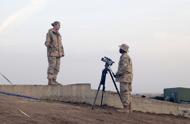 U.S. Air Force SENIOR AIRMAN Adrian Smith (right), a videographer with the 332nd Expeditionary Communications Squadron, interviews STAFF SGT. Kerrie Novak, of the 332nd Expeditionary Operations Support Squadron, for base documentation footage at Balad Air Base, Balad, Iraq, on Feb. 10, 2005. (U.S. Air Force PHOTO by STAFF SGT. Neal Joiner) (Released)