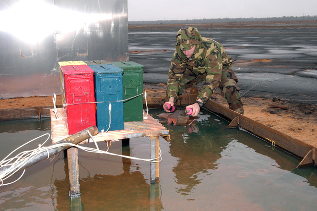 U.S. Air Force AIRMAN 1ST Clas Daniel S. Garrett, an explosives ordnance disposal technician assigned to the the 96th Civil Engineering Squadron, places two thermite grenades in the fire pan before an FMU-143 fuse test at Range B-71 at Eglin Air Force Base, Fla., on Feb. 25, 2005. The test was conducted to check what hazards the fuses would present in case of an accidental fire. (PHOTO by Craig C. McDonnell, CIV) (Released)
