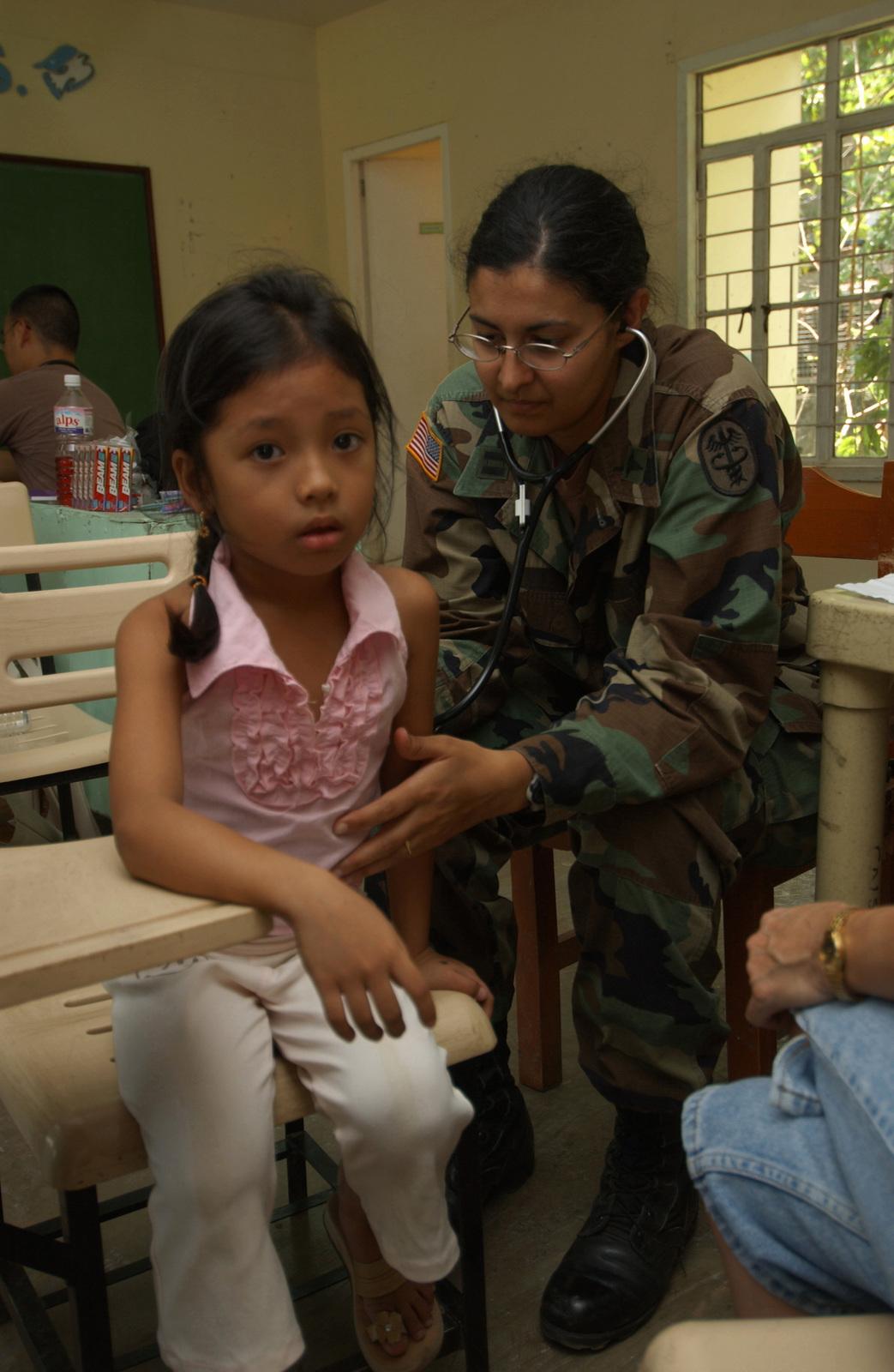 U S  Army Captain Harkritin Gydee checks the health of a