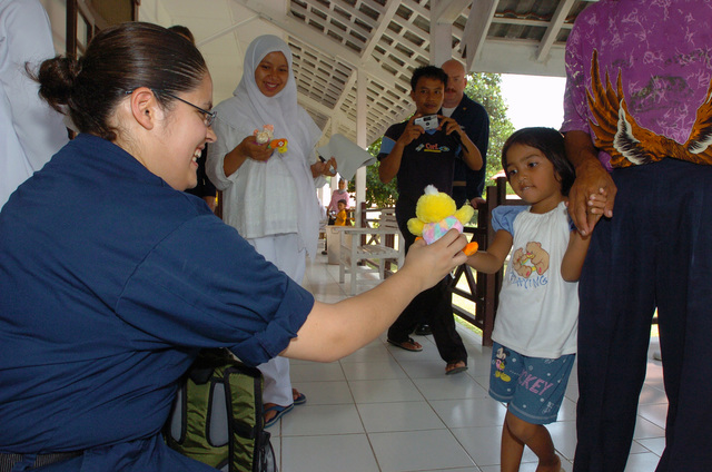US Navy (USN) Hospital Corpsman Third Class (HM3) Triselda Penberthy, assigned to the Military Sealift Command (MSC) Hospital Ship USNS MERCY (T-AH 19) [not shown], passes out toys to Indonesian children after instructing a class for Indonesian Nurses at Tentera Nasional Indonesia Military Hospital in Banda Aceh, Indonesia. The MERCY is currently off the waters of Indonesia in support of Operation UNIFIED ASSISTANCE the humanitarian relief effort to aid the victims of the Tsunami that struck Southeast Asia on December 26, 2004