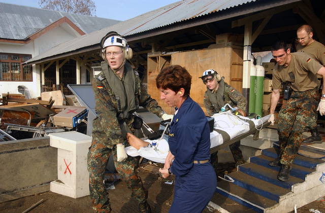 US Navy (USN) Commander (CDR) Karen McDonald (center), Assistant Director of Nursing, Military Sealift Command (MSC) Hospital Ship USNS MERCY (T-AH 19) [not shown], assisted by members of the German military as they carry an Indonesian patient to an awaiting USN helicopter for transport to the MERCY. The MERCY is currently off the waters of Indonesia in support of Operation UNIFIED ASSISTANCE the humanitarian relief effort to aid the victims of the Tsunami that struck Southeast Asia on December 26, 2004