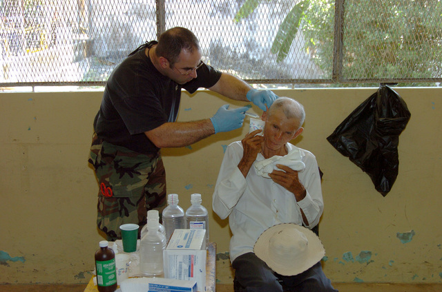 U.S. Air Force SENIOR AIRMAN Brad Karin (left), 142nd Fighter Wing Medical Group, Oregon Air National Guard (ORANG), cleans out the ears of a local in Sabana Grande, Panama, on March 7, 2005, during a Medical Readiness Training Exercise (MEDRETE) in support of New Horizons 05. (U.S. Army photo by Juan Torres-Diaz) (Released)