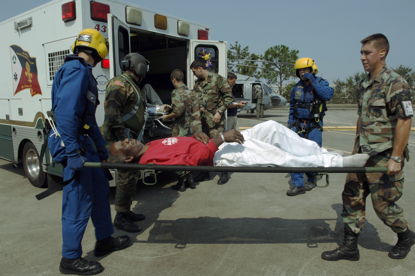 US Army (USA) National Guard Soldiers help to transport an injured man from an ambulance to an awaiting helicopter near the New Orleans Superdome while conducting humanitarian assistance operations following Hurricane Katrina. The USA is assisting in humanitarian assistance operations, led by the Federal Emergency Management Agency (FEMA), in conjunction with the Department of Defense (DOD)