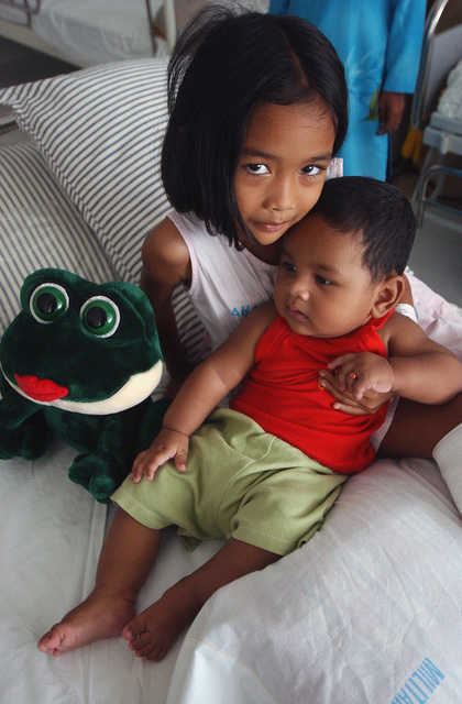 An Indonesian girl holds her little brother and a donated stuffed animal at Abizad Hospital in Banda Aceh, Indonesia, after returning from the Military Sealift Command (MSC) Hospital Ship USNS MERCY (T-AH 19) [not shown] for follow up treatment after having her left leg amputated. The MERCY is currently off the waters of Indonesia in support of Operation UNIFIED ASSISTANCE the humanitarian relief effort to aid the victims of the Tsunami that struck Southeast Asia on December 26, 2004