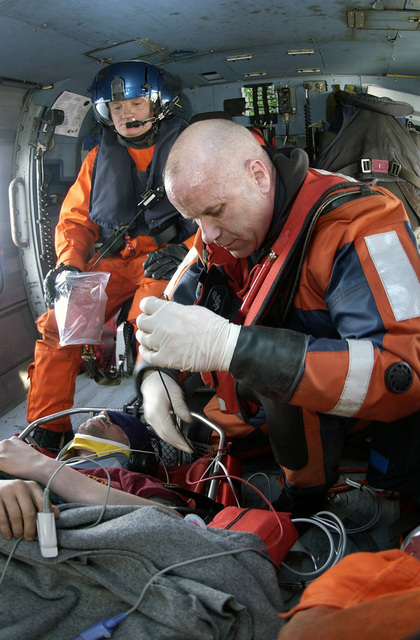 US Coast Guard (USCG) PETTY Officer First Class (PO1) Brian Laubenstein (right), Rescue Swimmer, Coast Guard Air Station (CGAS) Cape Cod, monitors an injured fisherman's vitals inside the cabin of an USCG HH-60J Jayhawk medium-range recover helicopter during the medical evacuation to Massachusetts General Hospital