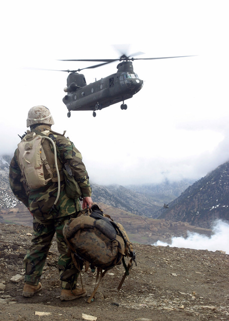 US Marine Corps (USMC) First Sergeant (1SGT) Vincent Santiago, assigned to Kilo Company, 3rd Battalion, 3rd Marine Regiment, waits as a US Army (USA) CH-47 Chinook helicopter approaches a landing zone site located in the mountainous vicinity of Methar Lam, Afghanistan, during Operation Mavericks, where USMC Marines assigned to 3rd Battalion, 3rd Marines are conducting Security and Stabilization Operations (SASO) in support of Operation ENDURING FREEDOM