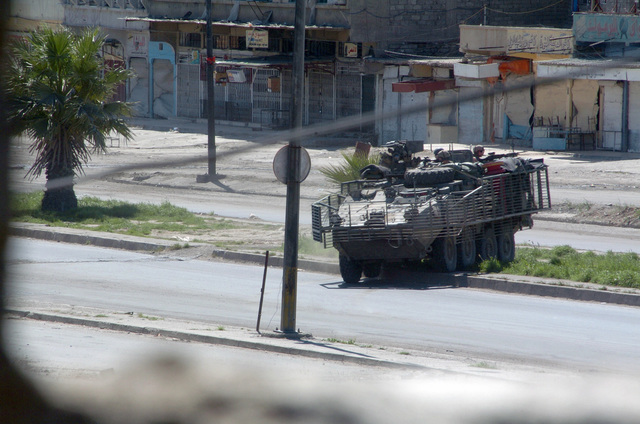 US Army (USA) Stryker, Alpha (A) Company, 1ST Battalion (BN), 24th Infantry Regiment (INF REGT), Fort Lewis, Washington (WA), patrols the street of Mosul, Iraq, during Operation IRAQI FREEDOM. The Stryker is equipped with a slat armor cage that will detonate anti-tank shaped charge warheads away from the vehicle