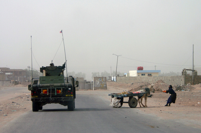 An Iraqi woman tries to desperately to move her donkey, giving the right of way to a US Army (USA) medium armored High-Mobility Multipurpose Wheeled Vehicle (HMMWV) with members of the 940th Military Police (MP), Kentucky Army National Guard (KYARNG). The MPs dispatched to break-up an unauthorized police checkpoint located in the city of Najaf during Operation IRAQI FREEDOM