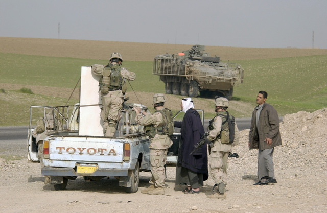 US Army (USA) Soldiers from 2nd Platoon (PLT), Bravo (B) Company (CO), 1ST Battalion (BN), 5th Infantry (INF), 25th Infantry Division (ID) (Stryker Brigade Combat Team (SBCT)) conduct a vehicle search at a traffic control point (TCP) during a patrol near Mosul, Iraq. In the background sits a USA M1126 Stryker Infantry Carrier Vehicle (ICV) with Slat Armor cage. The SBCT is assigned to Task Force Freedom supporting Operation IRAQI FREEDOM