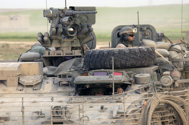 US Army (USA) Soldiers from 2nd Platoon (PLT), Bravo (B) Company (CO), 1ST Battalion (BN), 5th Infantry (INF), 25th Infantry Division (ID) (Stryker Brigade Combat Team (SBCT)), scans the horizon for threats from a USA M1126 Stryker Infantry Carrier Vehicle (ICV), with Slat Armor cage, while on patrol near Mosul, Iraq. The SBCT is assigned to Task Force Freedom supporting Operation IRAQI FREEDOM