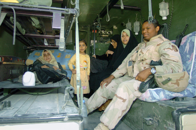 Eklas Abbas (left), a young Iraqi woman injured during a battle between US Marines and insurgents, back in August 2004, is taken by a medically equipped High-Mobility Multipurpose Wheeled Vehicle (HMMWV) to a Polish hospital in Karbarla, Iraq along with her mother, sister and niece during Operation IRAQI FREEDOM. There, she will undergo reconstructive surgery to the remainder of her legs, lost due to an unexploded mortar round crashing through her bedroom wall while she was sleeping. US Army (USA) SPECIALIST Fourth Class (SFC) Angela Walker (right) a Licensed Practical Nurse (LPN) from the Task Force 198th Battalion Aid Station (BAS) will oversee her care and support during the trip