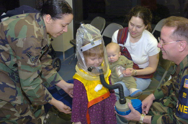 U.S. Air Force AIRMAN 1ST Class Jessica Harrell (left), of the 51st Communications Squadron, and MASTER SGT. Paul Pellow, of the 51st Operations Support Squadron, demonstrate how to properly place a childs gas mask on Gwyneth James while her mother, Jennifer. and her brother, Henry, look on during a Non-Combatant Evacuation Operations during an Operational Readiness Inspection at osan Air Base, Korea, on April 1, 2005. (U.S. Air Force PHOTO by SENIOR AIRMAN Chris Willis) (Released)
