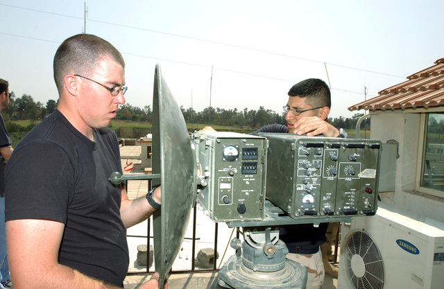 U.S. Air Force SENIOR AIRMAN Christopher Decorte, and STAFF SGT. Rocky Cabrera, members of the 506th Expeditionary Communications Squadron set up a mobile line of sight microwave tropo satellite support radio system at the U.S Emabassy at Kirkuk, Iraq, on April 1, 2005. (U.S. Air Force PHOTO by Matthew Lohr) (Released)